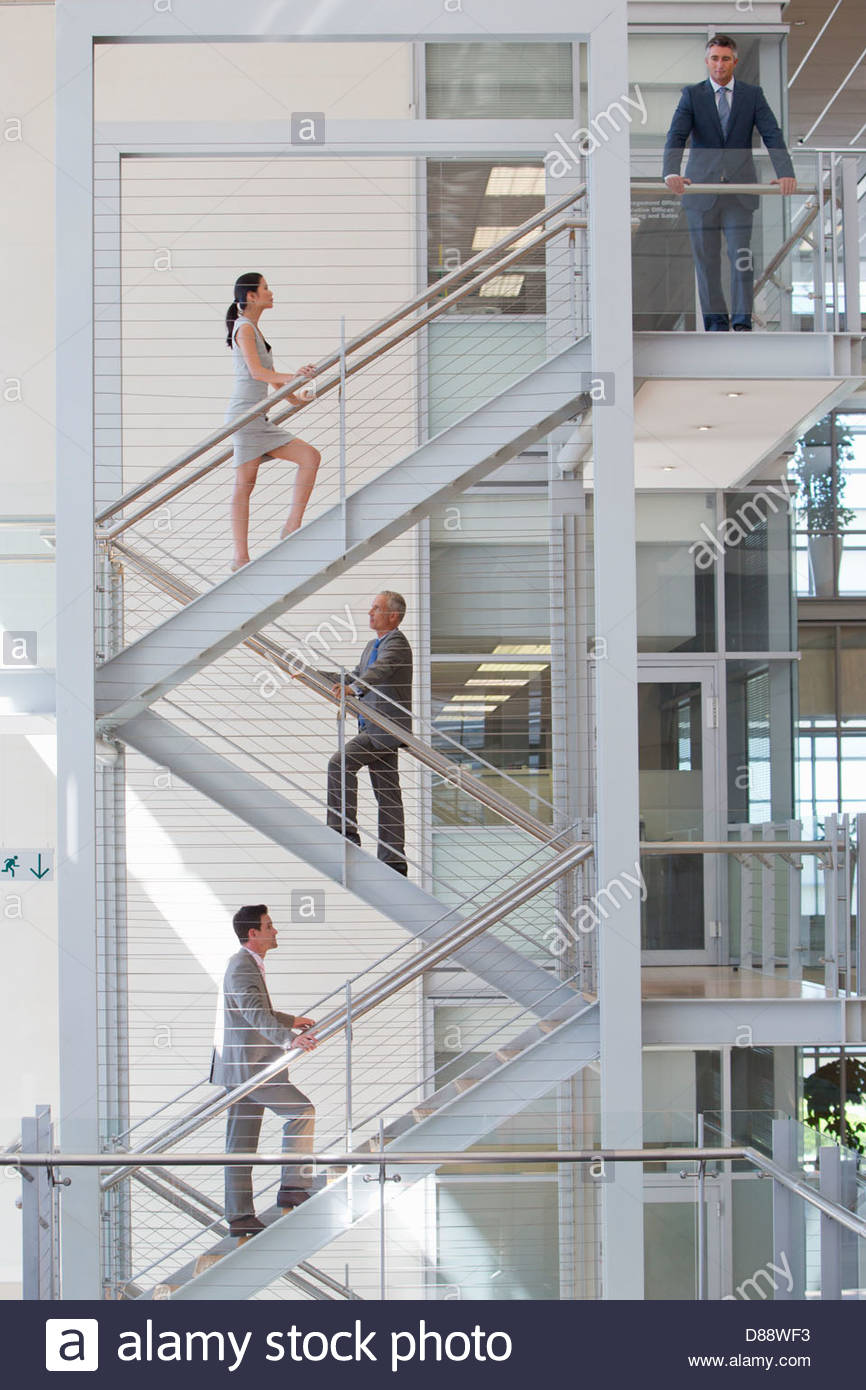 Business people ascending stairs in office - Stock Image