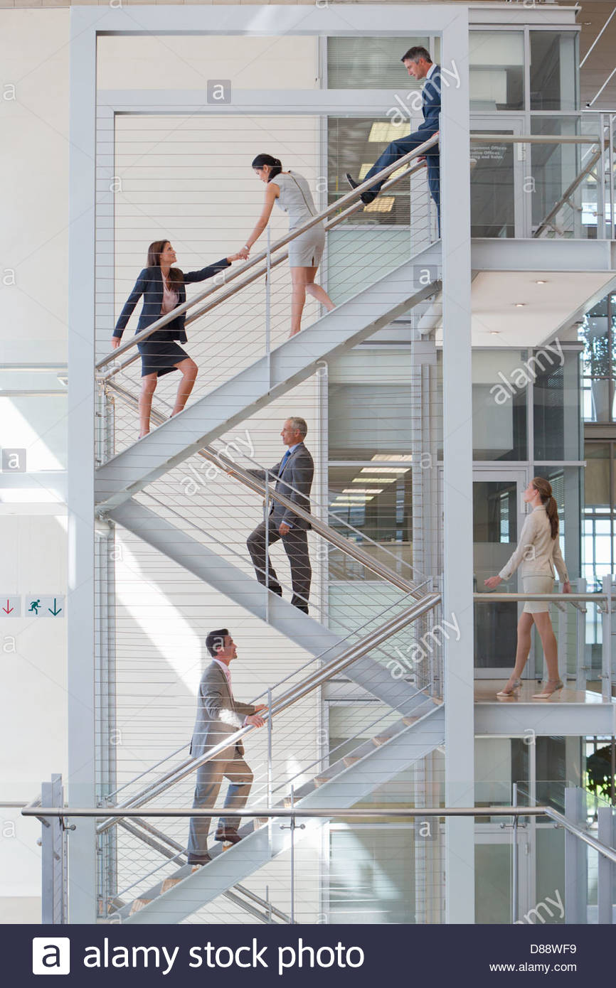 Businessman blocking businesswomen on stairs in office - Stock Image
