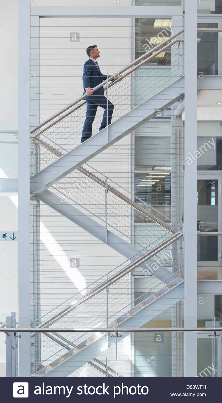 Businessman ascending stairs in office - Stock Image