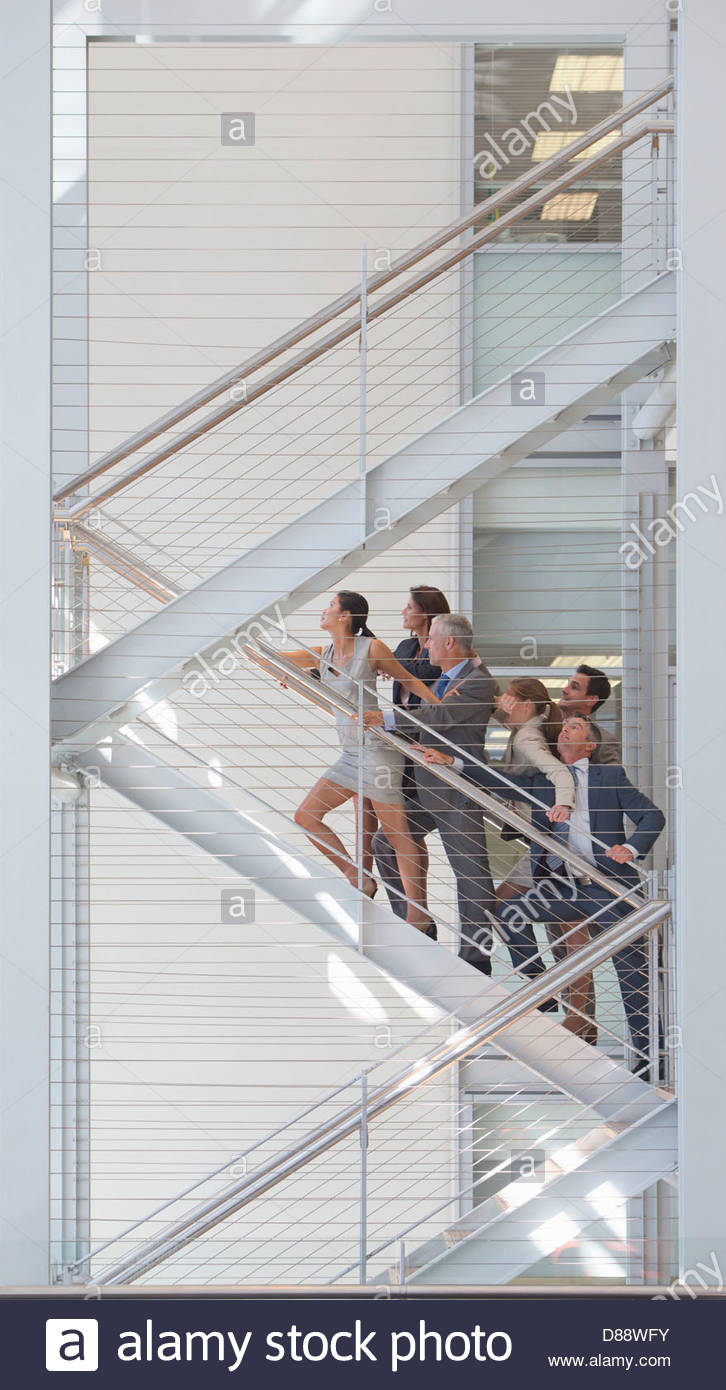Connected business people ascending stairs in office - Stock Image