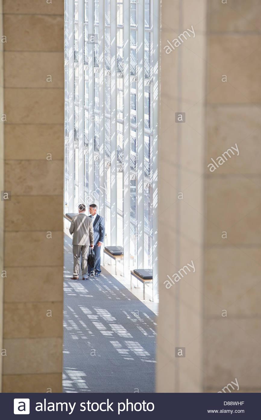 Businessmen talking in lobby of modern office - Stock Image