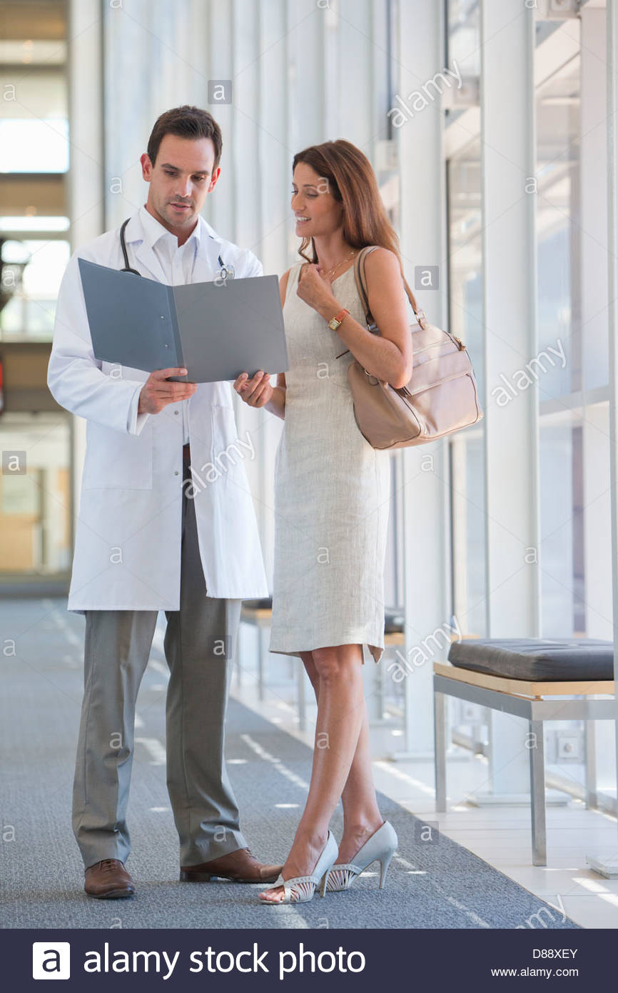Doctor and patient reviewing medical chart in hospital corridor - Stock Image