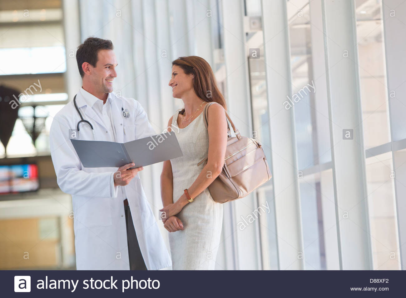 Smiling doctor and patient reviewing medical chart in hospital corridor - Stock Image
