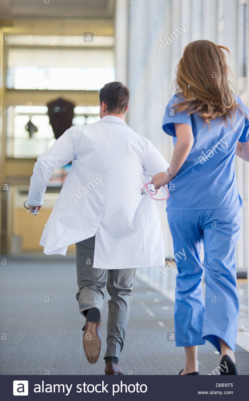 Doctor and nurse running down hospital corridor - Stock Image