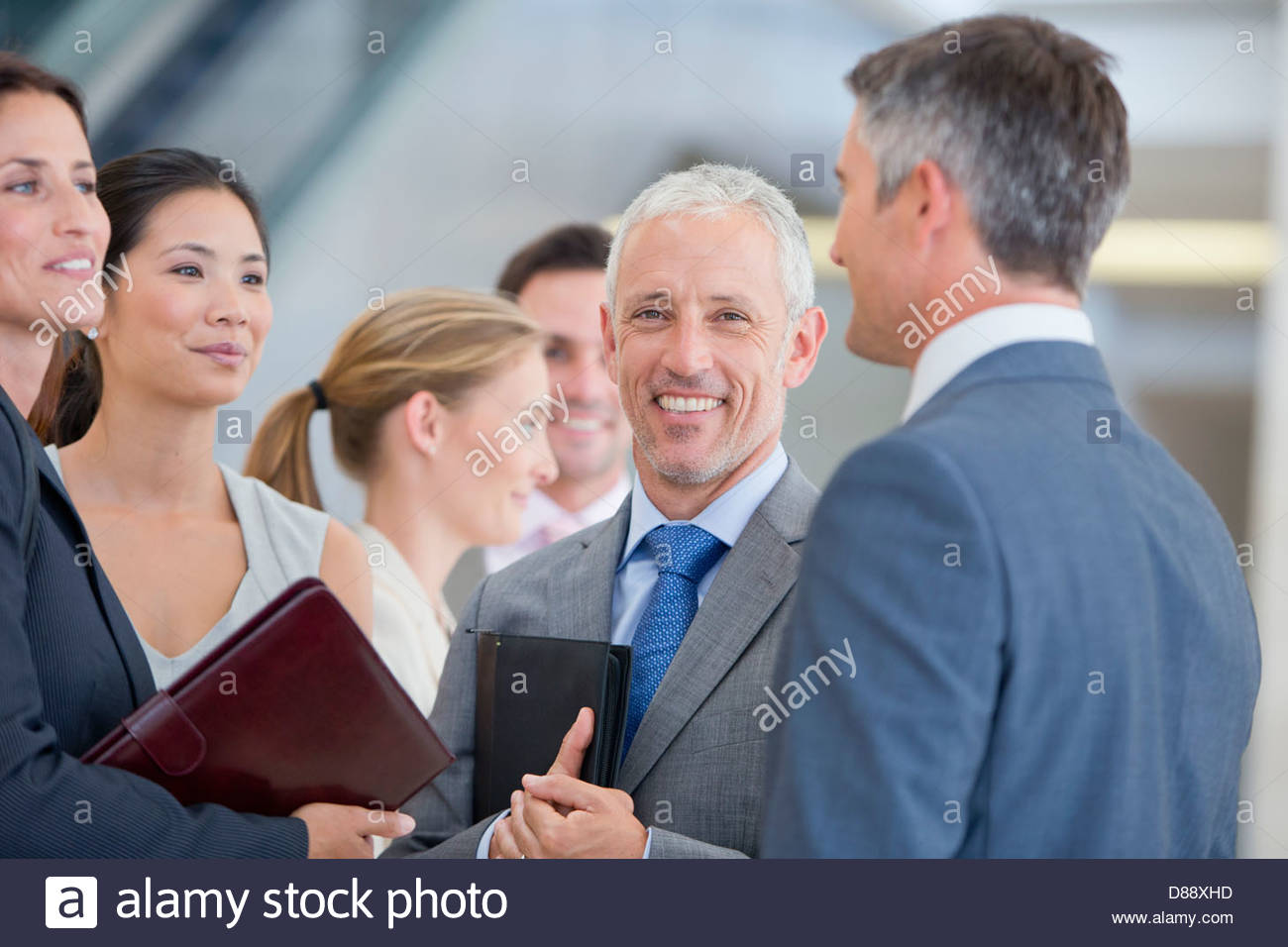 Portrait of smiling businessman among co-workers - Stock Image