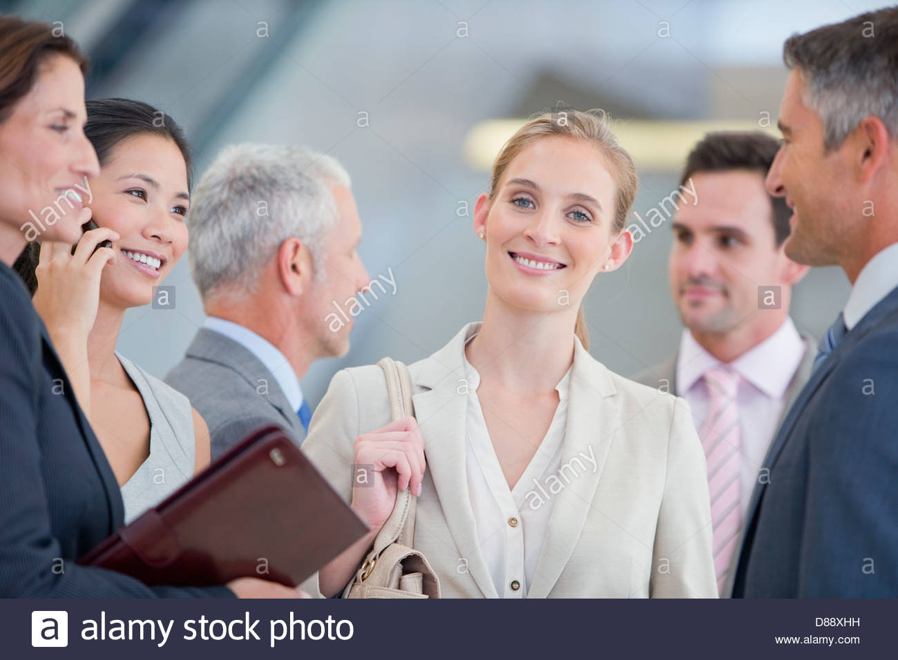 Portrait of smiling businesswoman among co-workers - Stock Image