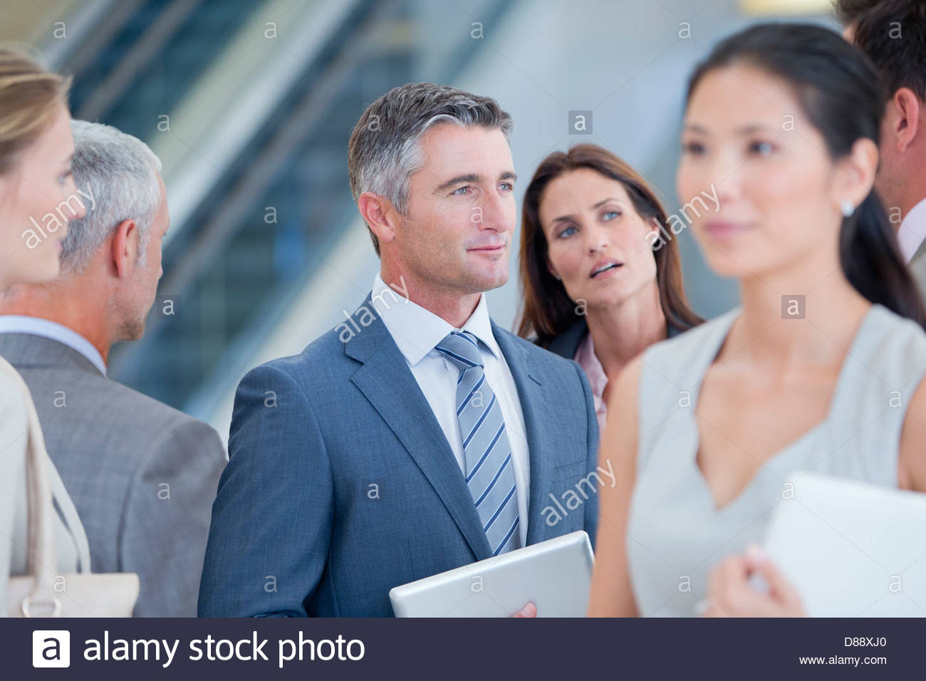 Serious businessman listening to co-worker - Stock Image