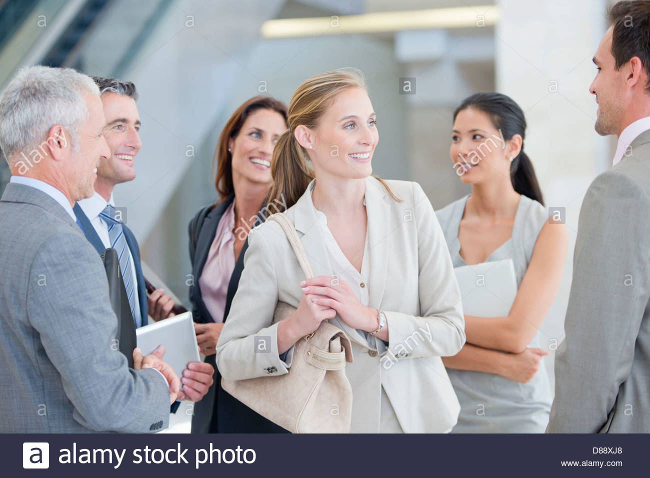 Smiling business people talking - Stock Image