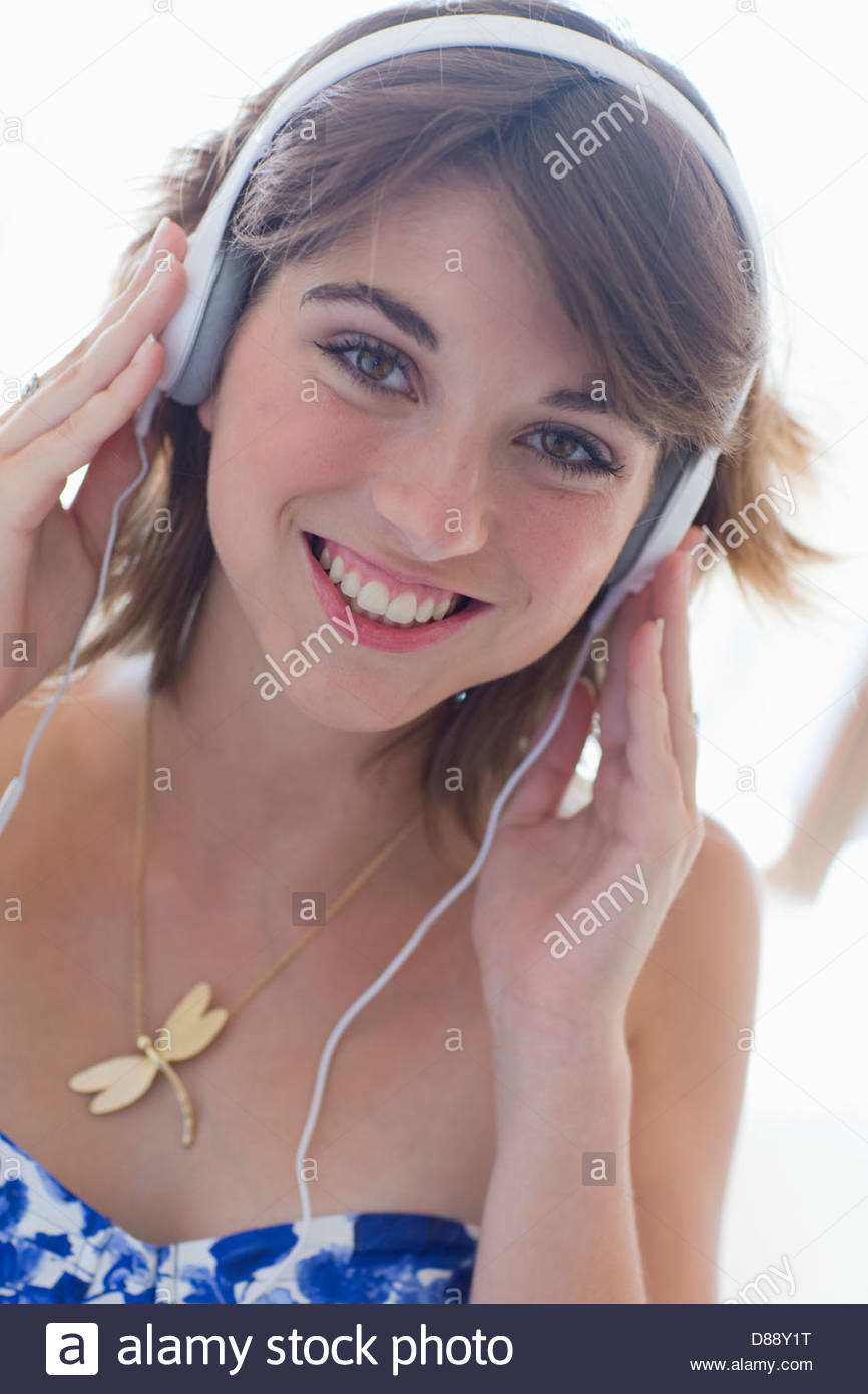 Close up portrait of smiling young woman wearing headphones Stock Photo