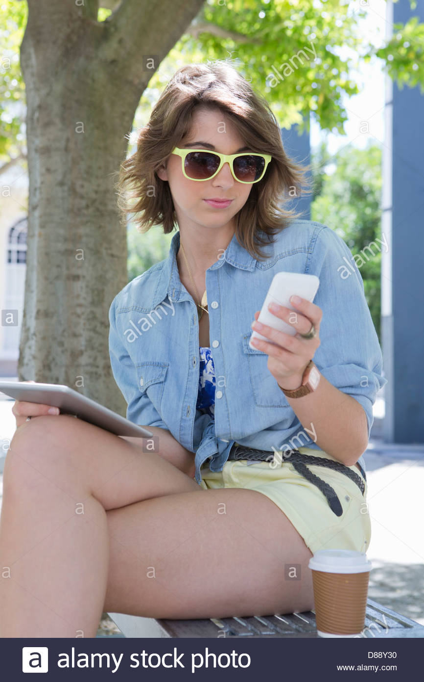 Young woman wearing sunglasses and using cell phone and digital tablet in park - Stock Image