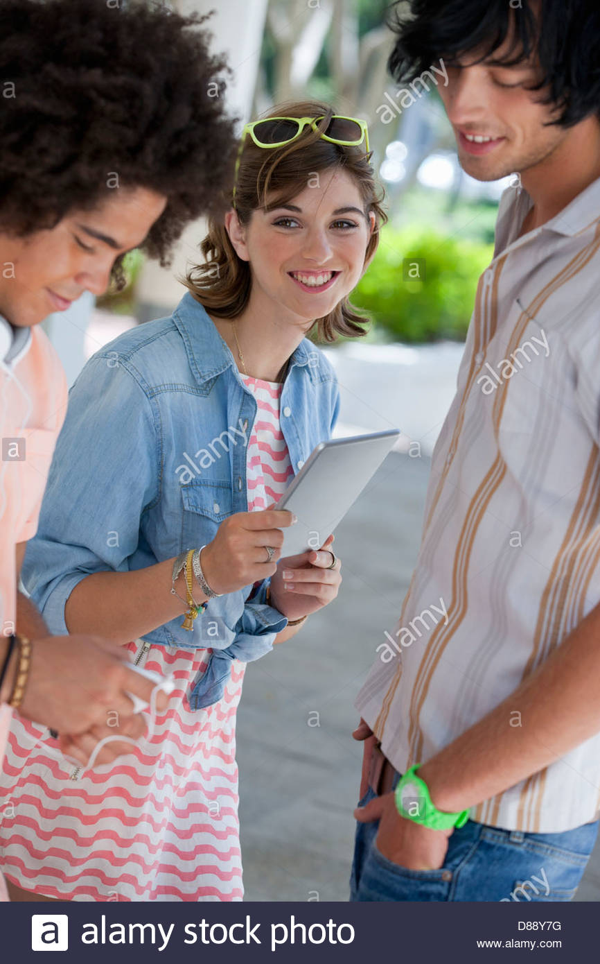 Smiling friends with cell phone and digital tablet - Stock Image