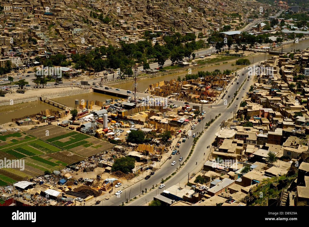 View from above of a Kabul road that runs alongside a river - Stock Image