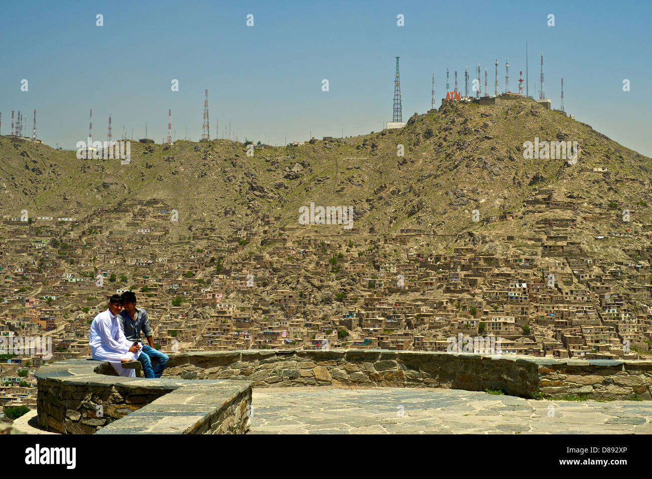 Kabul, Two Friends relax, with TV Hill in the background - Stock Image