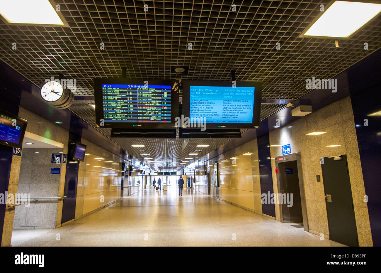 Electronic departure and arrival boards overhead in a long passageway at the Brussels Midi train station in Belgium. - Stock Image