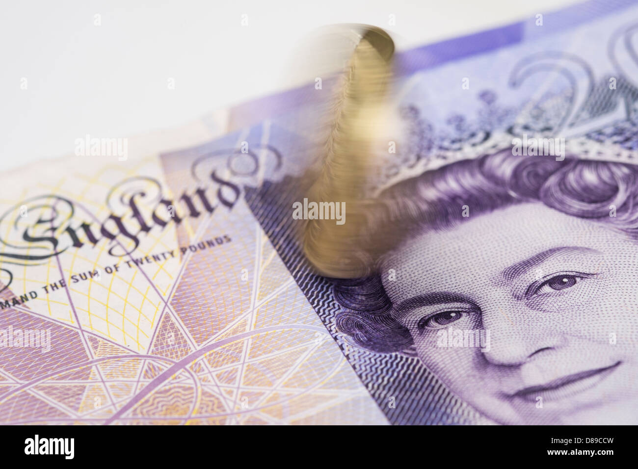A pound coin spinning on a twenty pound note. - Stock Image