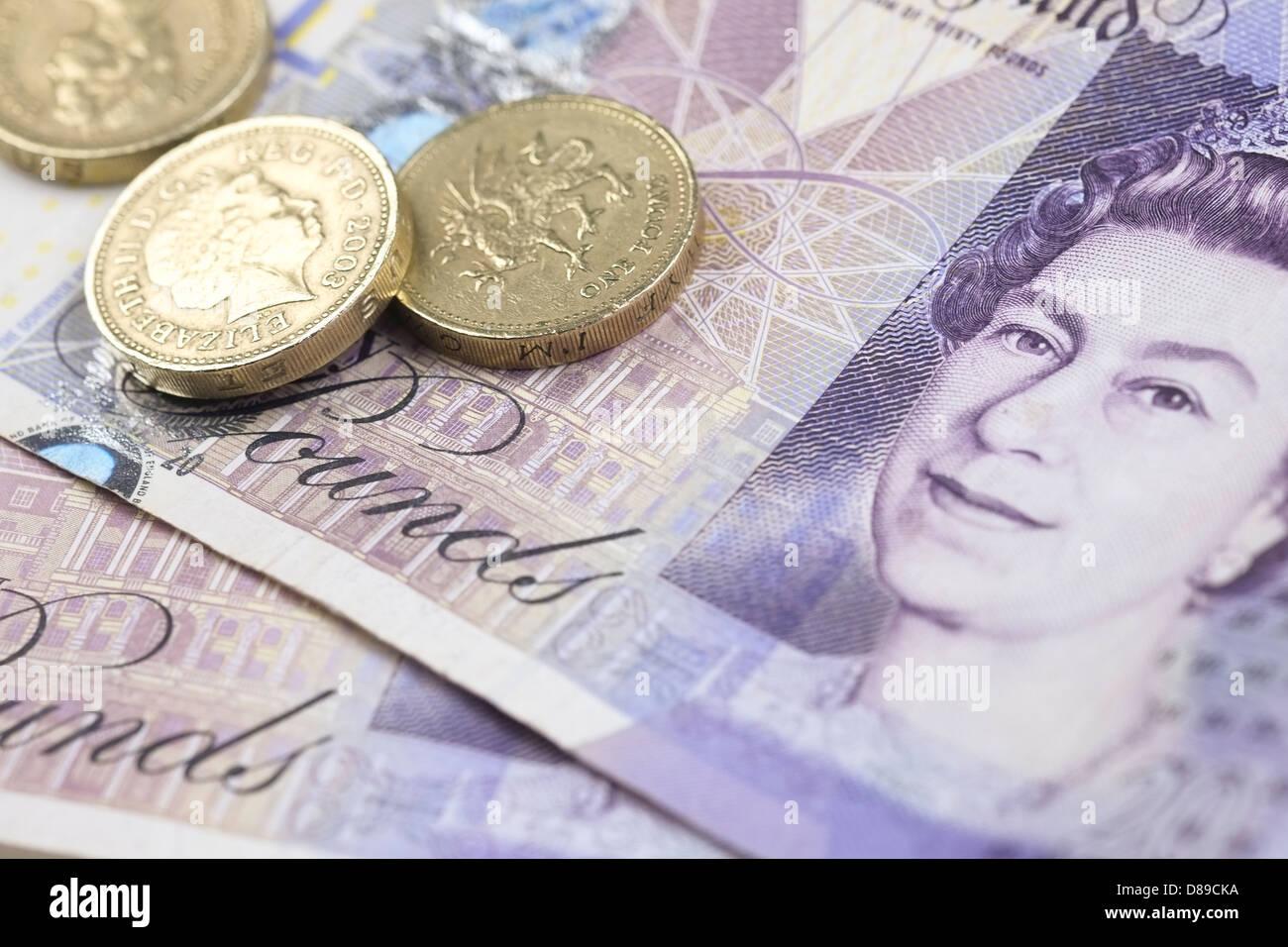 Three pound coins on a twenty pound note. - Stock Image
