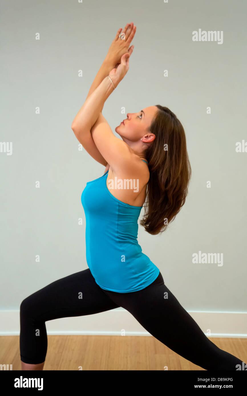 Warrior 1 with eagle yoga pose - Stock Image