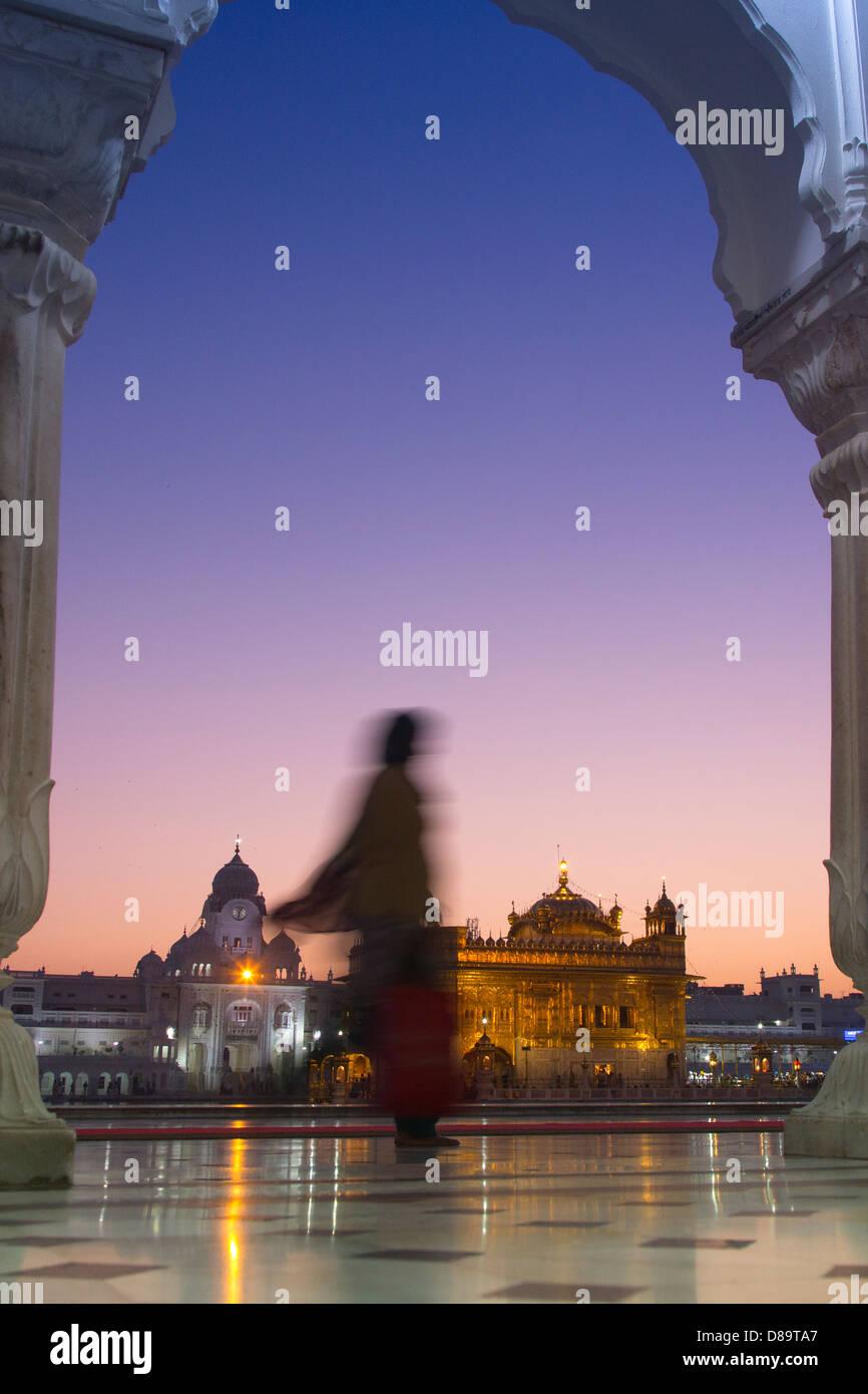 India, Punjab, Amritsar. Golden Temple illuminated at dusk with blurred woman walking past - Stock Image