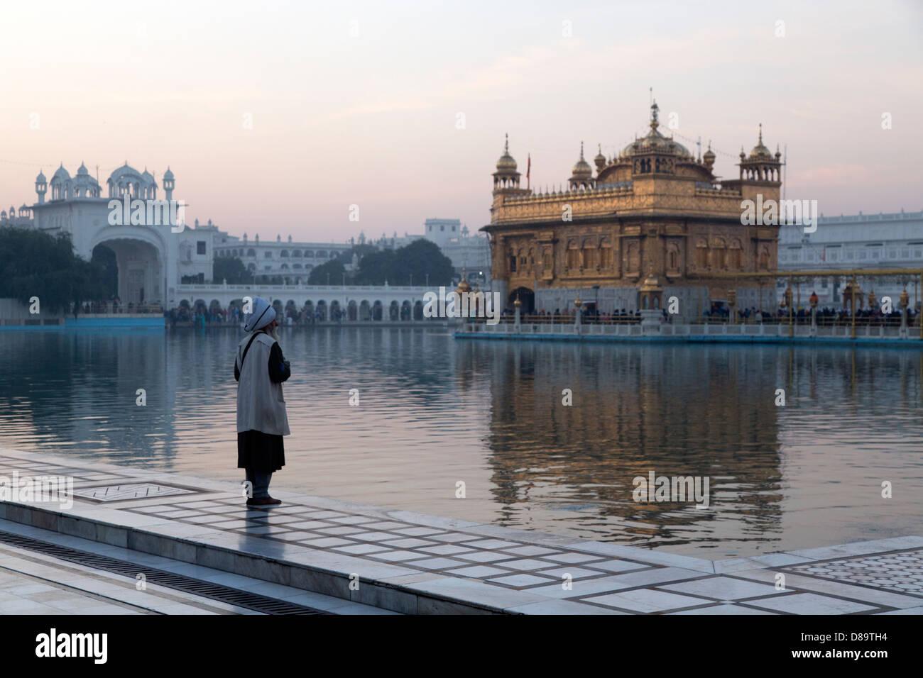 India, Punjab, Amritsar. golden Temple, Holy Man looking at temple at dawn - Stock Image