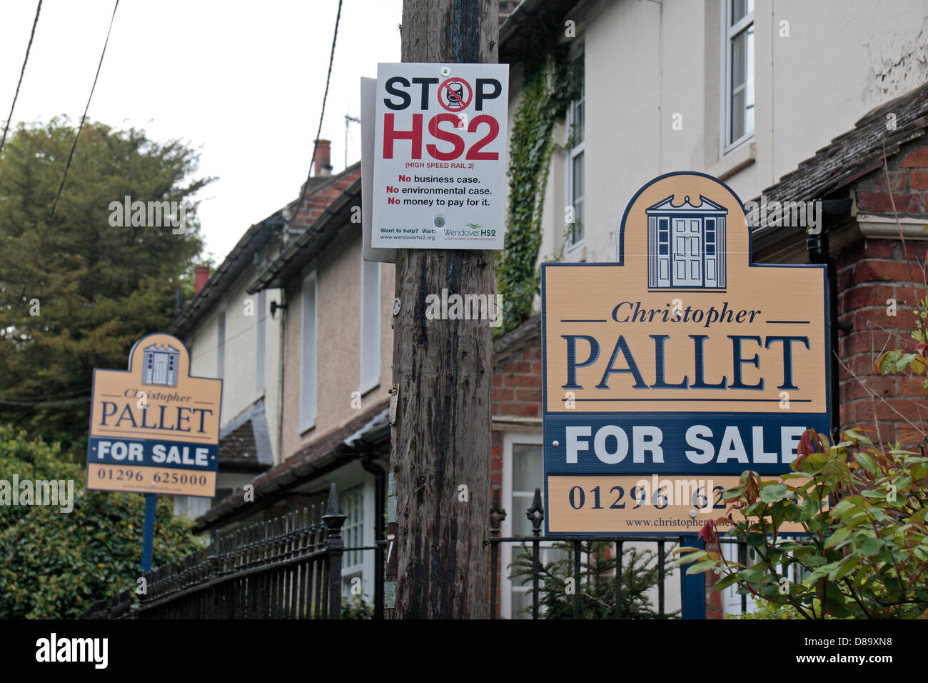 A 'Stop HS2' poster on a telephone pole close to two house 'for sale' signs, in Wendover, Buckinghamshire, - Stock Image