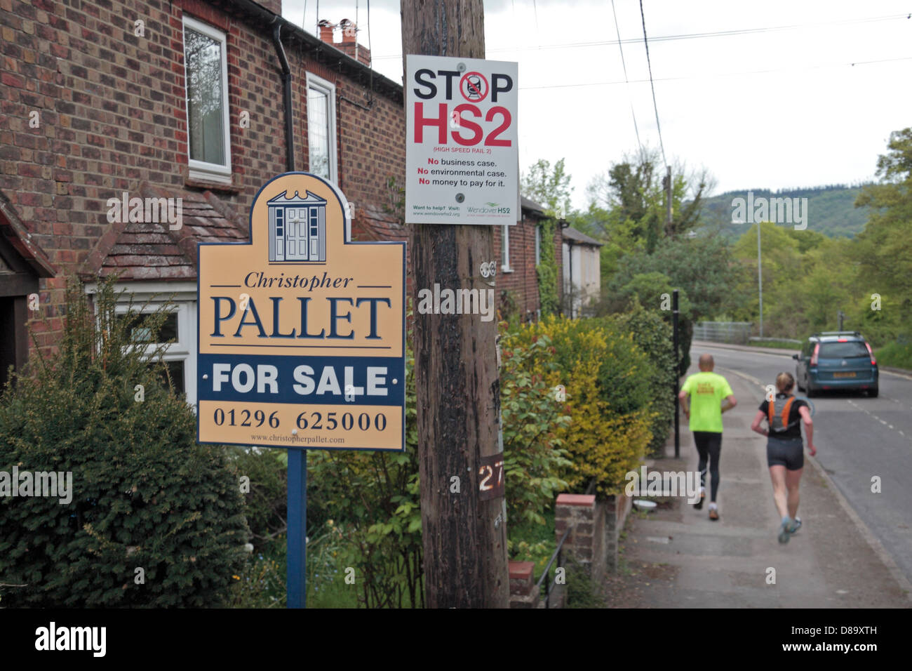 A 'Stop HS2' poster on a telephone pole beside a house 'for sale' sign, in Wendover, Buckinghamshire, - Stock Image