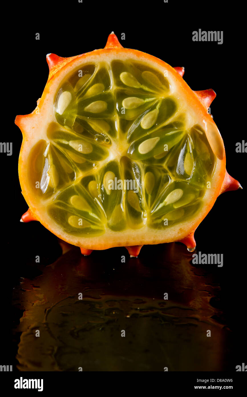closeup of a horned melon fruit cut open isolated on black - Stock Image