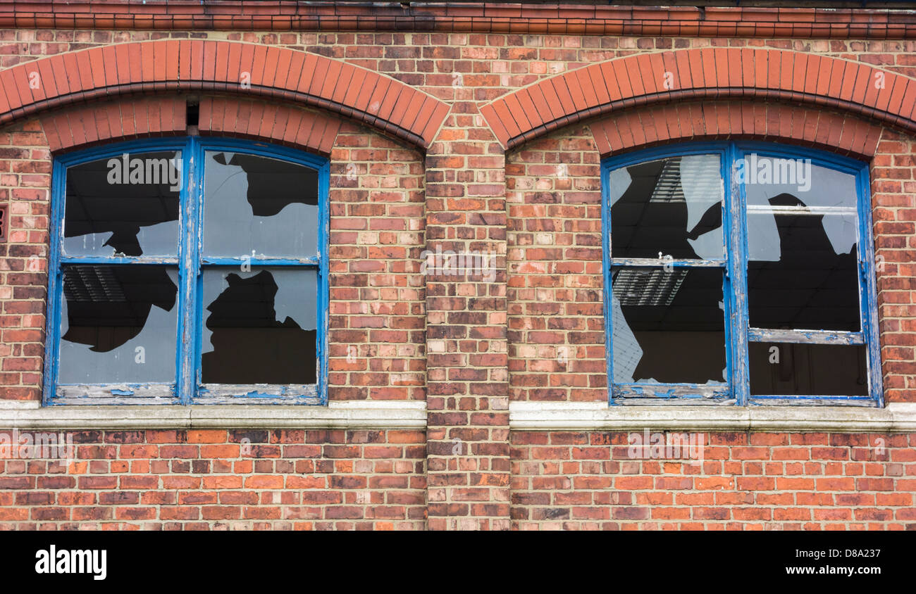 Broken windows in derelict factory - Stock Image