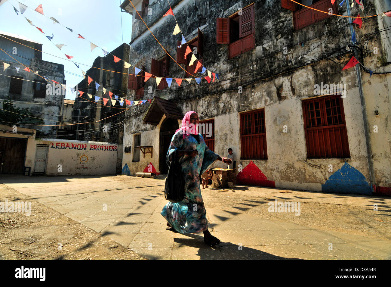 Muslim Young Woman Walking in the flags decorated streets of Stonecity, Zanzibar - Stock Image