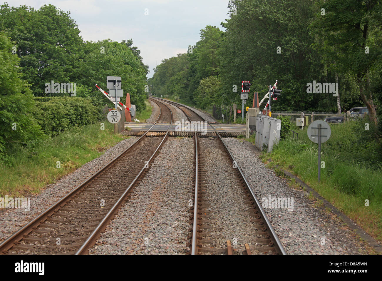 An Automatic Half Barrier Road Level crossing at Tangley Lane to the south of Guildford, on a very busy line. - Stock Image