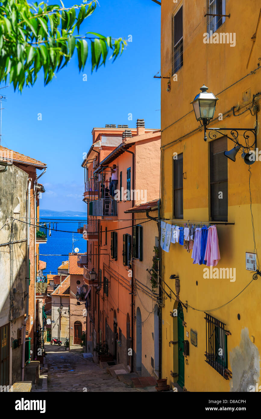 View of the sea from a small street in Porto Santo Stefano, Monte Argentario, Maremma, Grosseto Province, Tuscany, - Stock Image