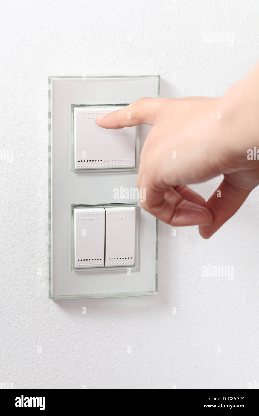 Woman hand operating a light switch - Stock Image