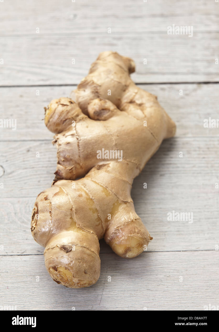 A fresh uncut ginger root on a rustic wood surface. - Stock Image