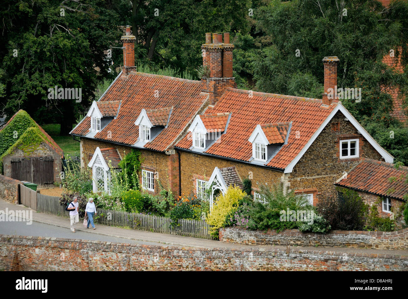 Red brick cottages with dormer windows and gardens in village of Castle Rising, Norfolk, England - Stock Image