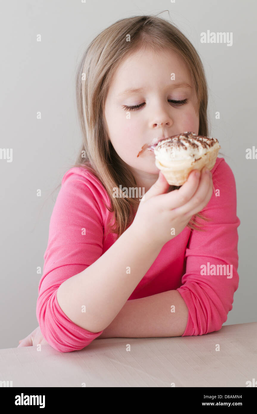 Indoor picture of the pretty girl eating the ice cream - Stock Image