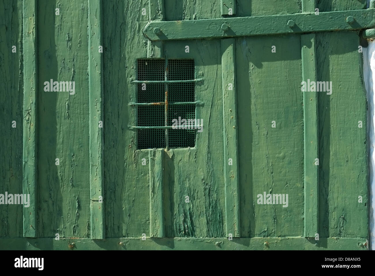 Barred window in green boathouse door Menorca, Spain - Stock Image
