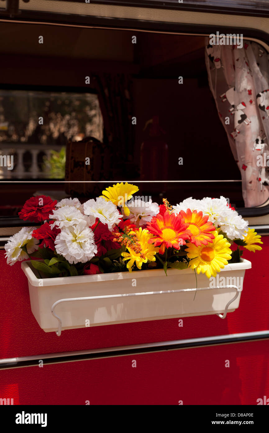 Windowbox with artifical flowers on the side window of a Volkswagen VW campervan - Stock Image
