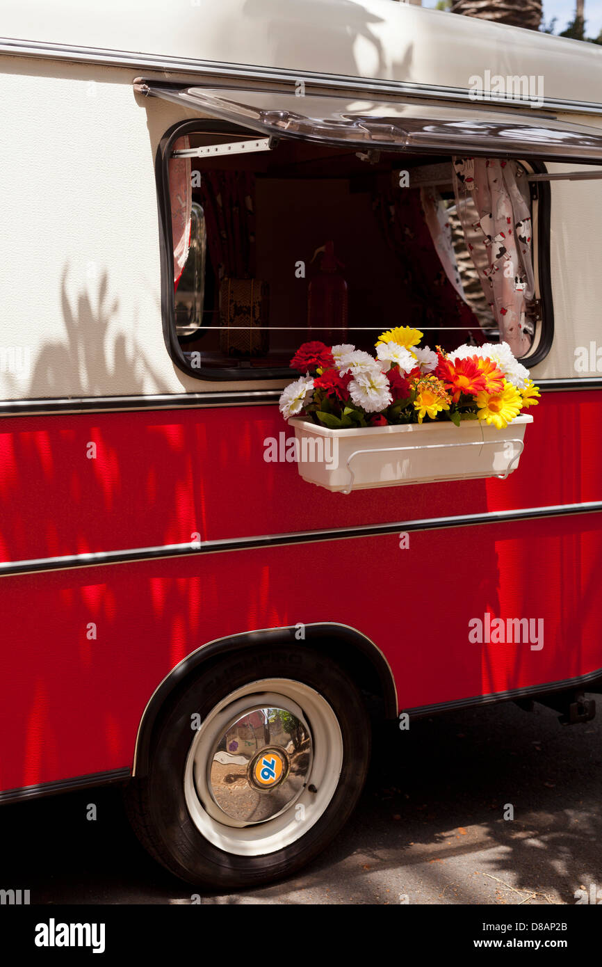 Windowbox with artificial flowers on the side window of a Volkswagen VW campervan - Stock Image
