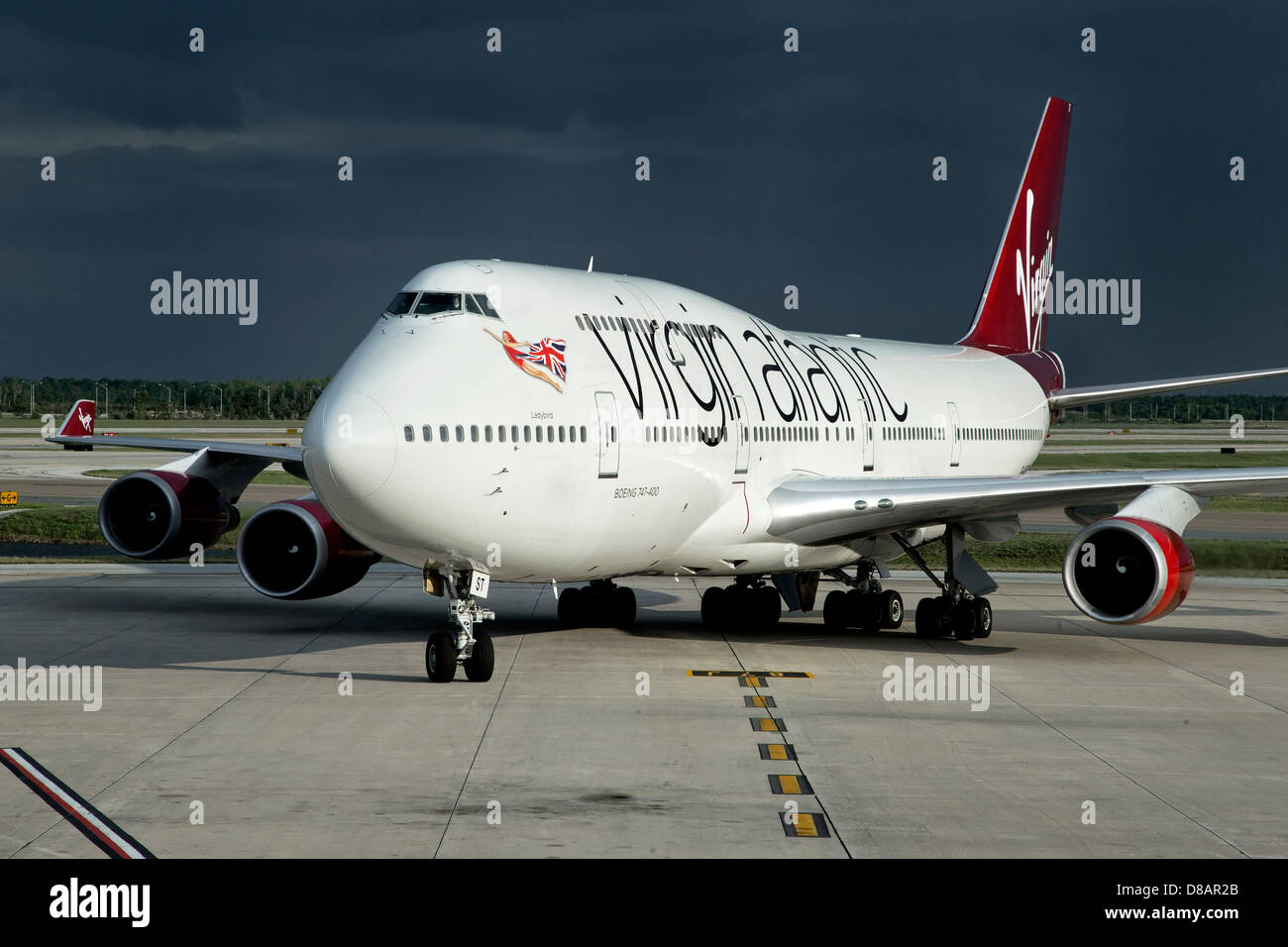 A Boeing 747 of Virgin Atlantic airways taxiing on to stand - Stock Image