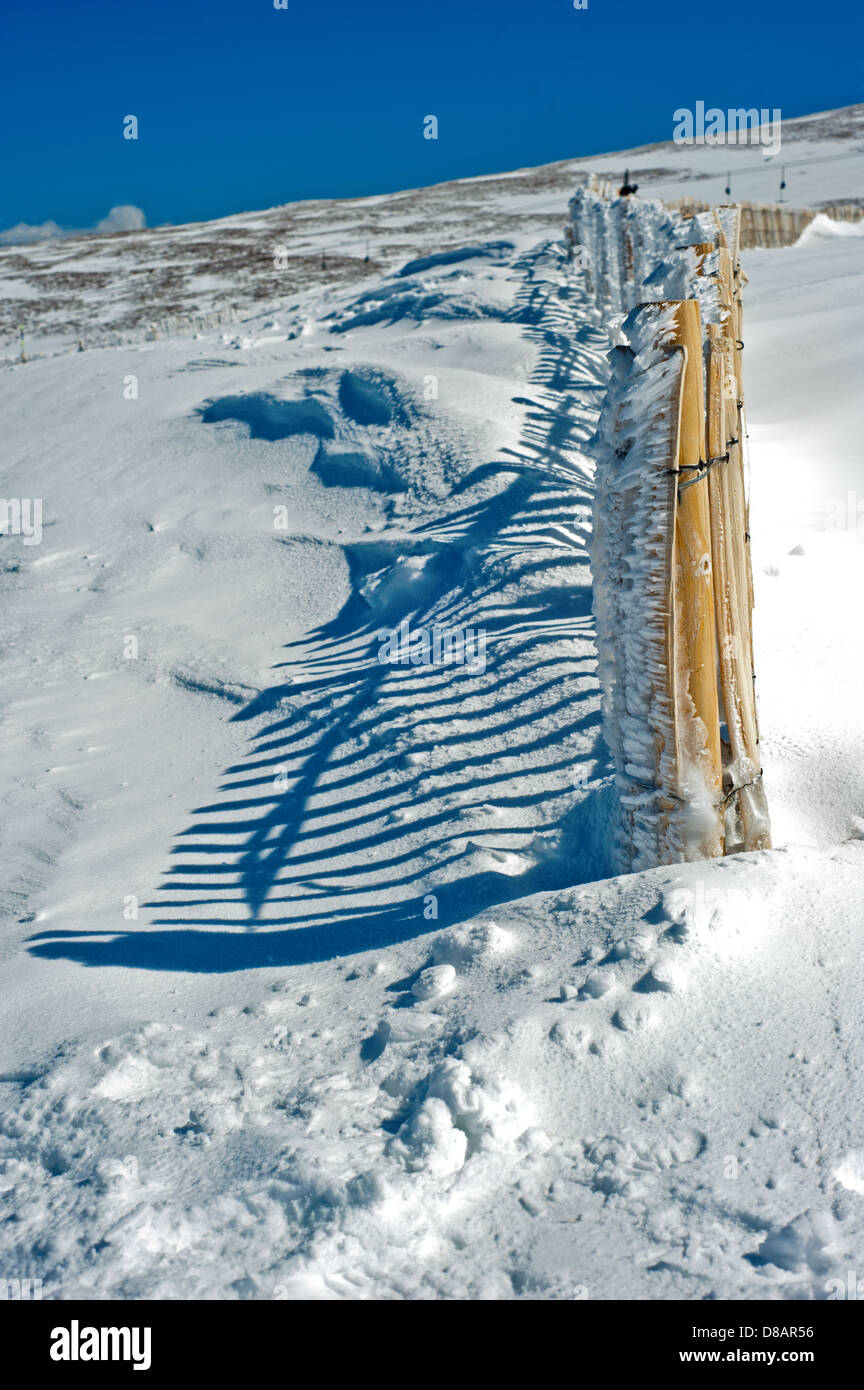 Fence on snow covered mountain with strong shadow - Stock Image