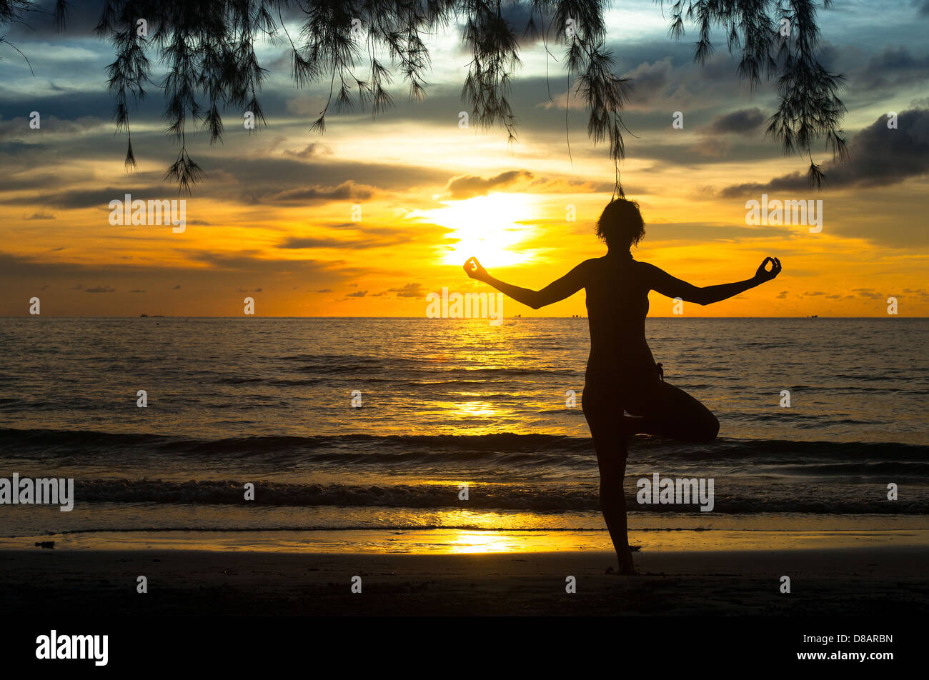 Woman practicing yoga on the beach during sunset. - Stock Image