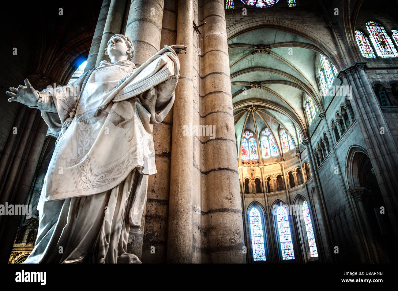 Interior of old catholic church in France, Europe. Statue of man and huge column in foreground with grand arch and - Stock Image