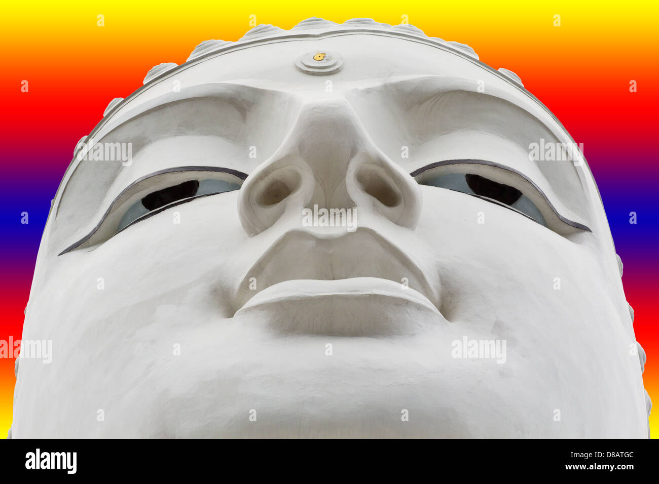 LARGE WHITE BUDDHA FACE WITH A COLOURED BACKGROUND - Stock Image