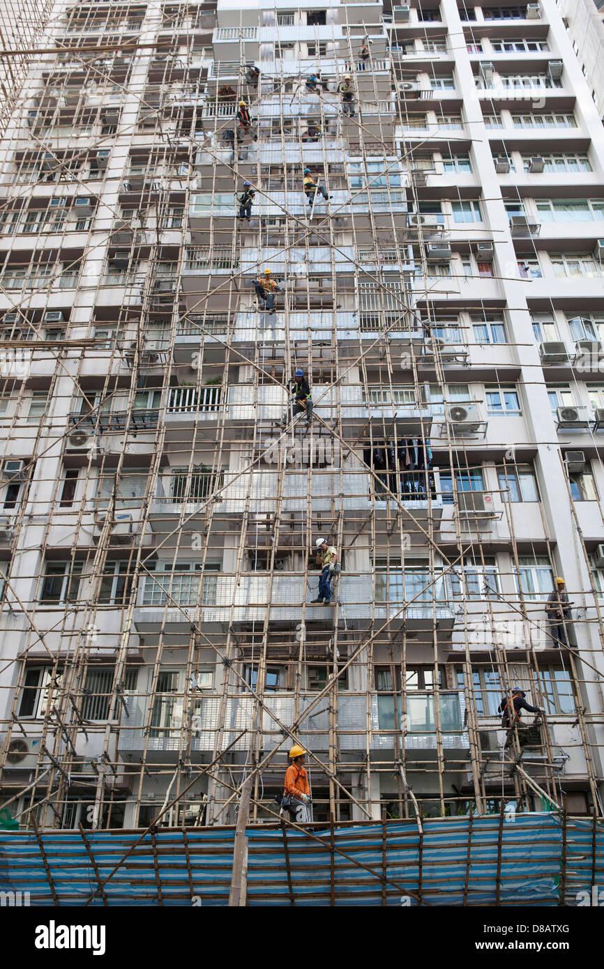 Builders using bamboo scaffolding in Hong Kong - Stock Image