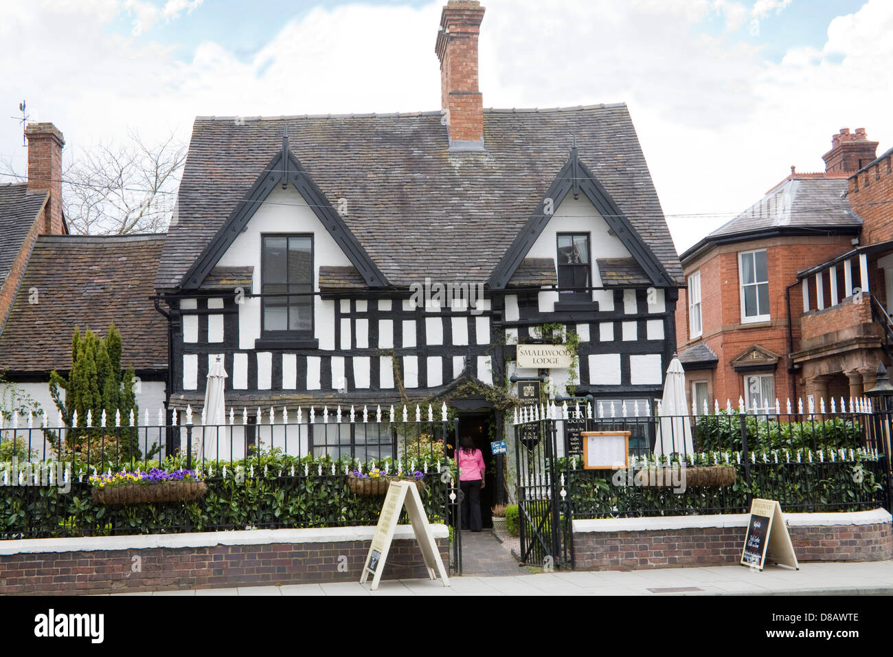Newport Shropshire England Visitor entering 17thc Smallwood Lodge Tea Rooms in a Grade 11 listed building with 19thc - Stock Image