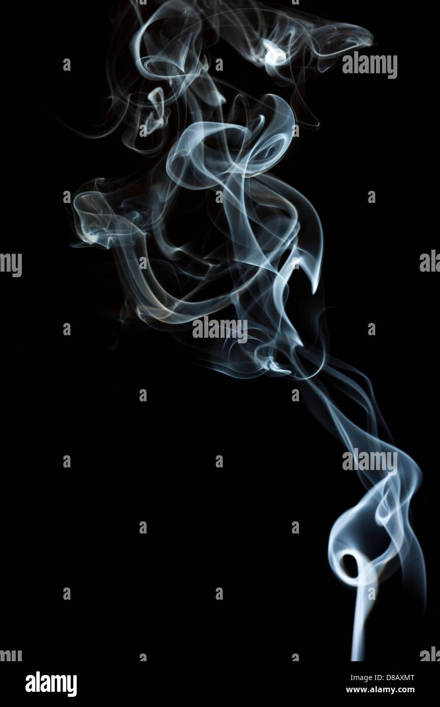 Whispy White Smoke against a black background - Stock Image