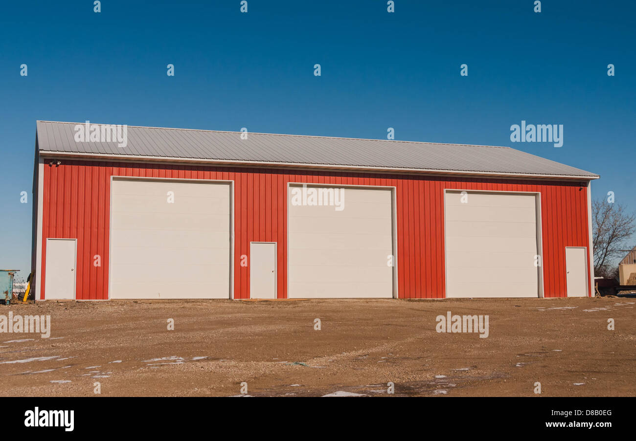 Small industrial warehouse with identical doors - Stock Image