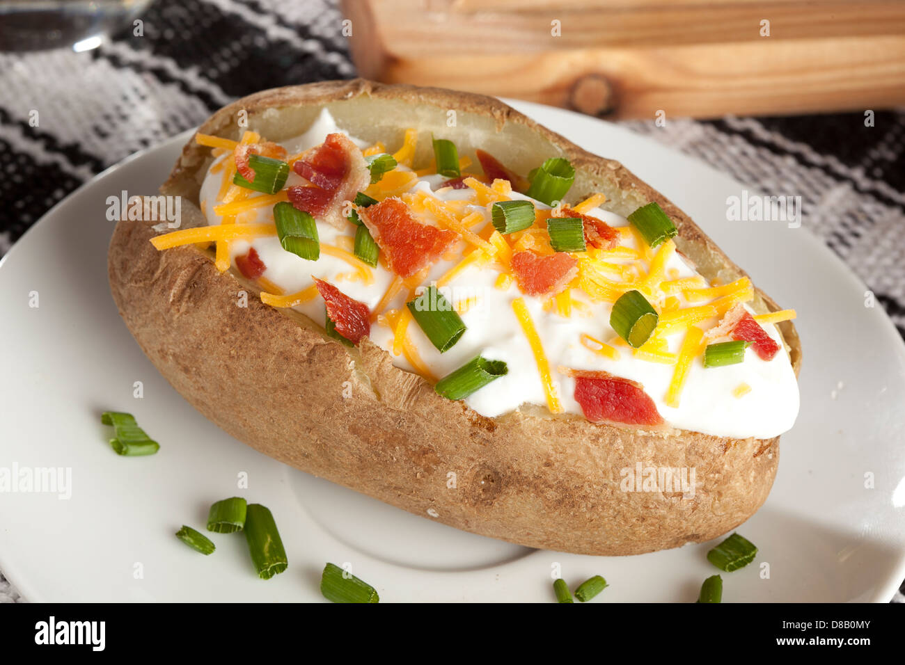 Hot Baked Potato with chives, cheese, and sour cream - Stock Image