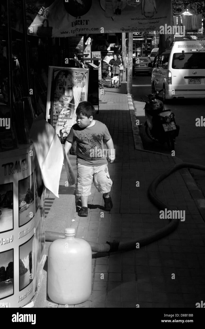 PATONG, PHUKET, THAILAND FEBRUARY 28 2012: Boy gazes inside hair salon on Banzann Road - Stock Image