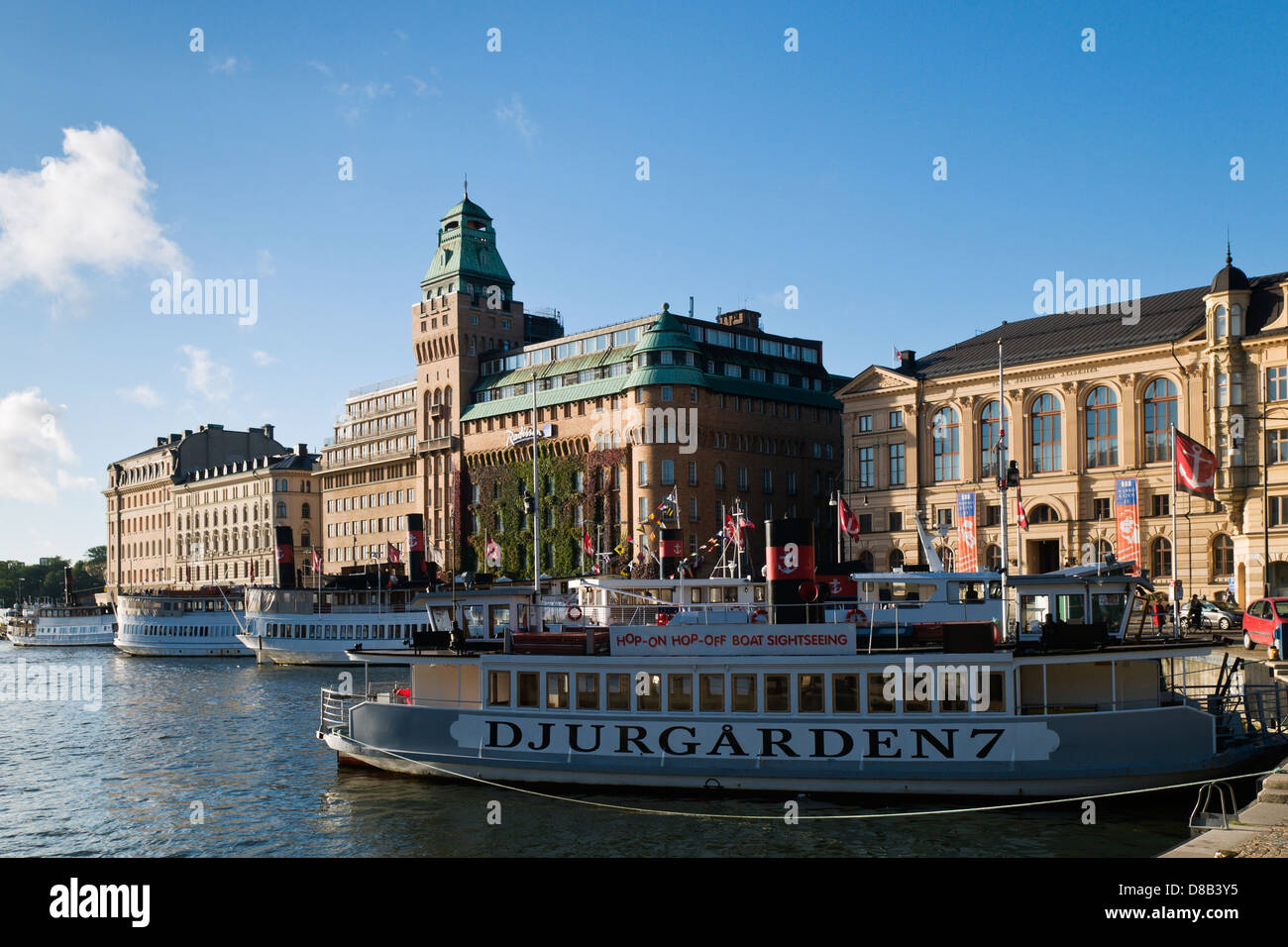 Djurgården ferry and SAS Radisson Hotel in Nybrohamnen. - Stock Image