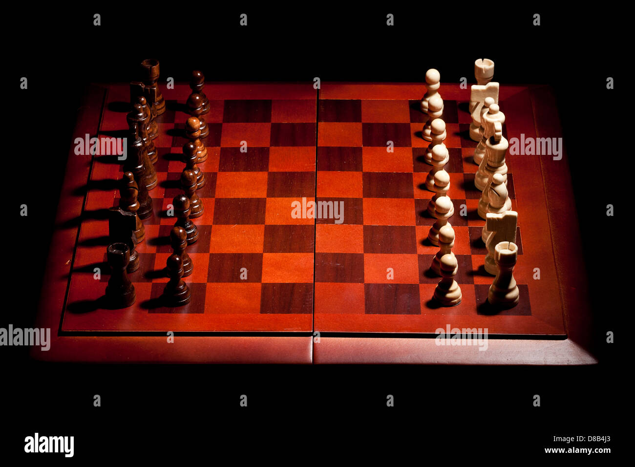 Classic Wooden Chessboard with Chess Pieces against a background - Stock Image